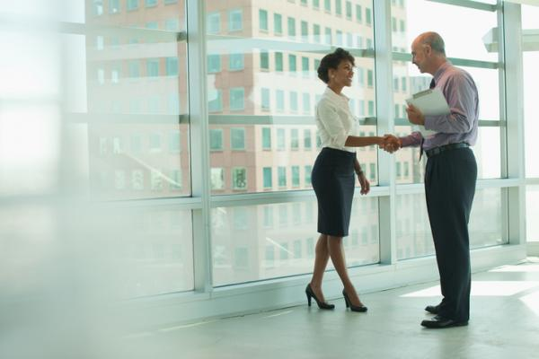Man and woman in business attire shaking hands in an office hallway