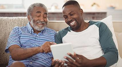 Grandfather and grandson looking at a tablet together.
